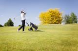 Golf player swinging club on fairway. poster