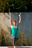 woman doing yoga outdoors in warrior one pose