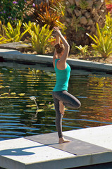 woman doing yoga outdoors in tree pose near water