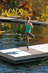young woman doing yoga outdoors in tree pose near water