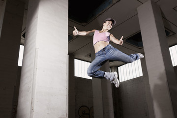 Female dancer jumping with thumbs up.