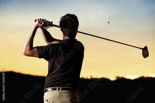 Fototapeta Golfer teeing off at sunset.