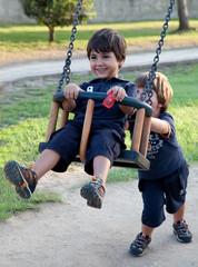 bambini giocano al parco con l'altalena