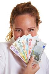Frau hinter Fächer aus Geldscheinen
