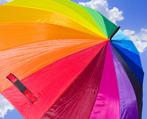 Rainbow-colored umbrella against the skies