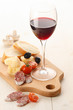 Wineglass with red wine and assortment of cheese and fruits on w