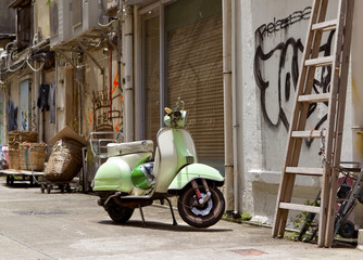 Classic green old scooter in back alley of downtown Hong Kong