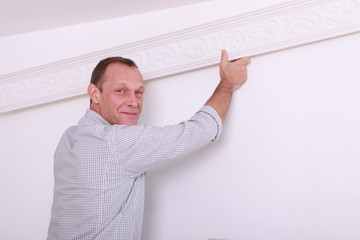 Decorator fixing coving to a ceiling