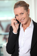 Smiling businesswoman using a telephone