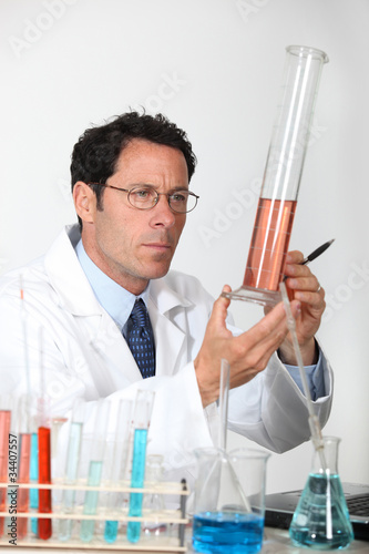 Laboratory technician examining liquid in a graduated cylinder