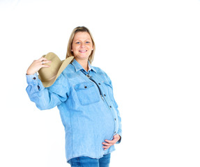 schwangere Frau im jeanshemd hält  cowboyhut in der hand