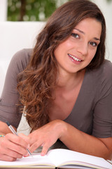 Long haired girl writing in a hardback notebook