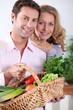 Couple smiling with vegetable basket.