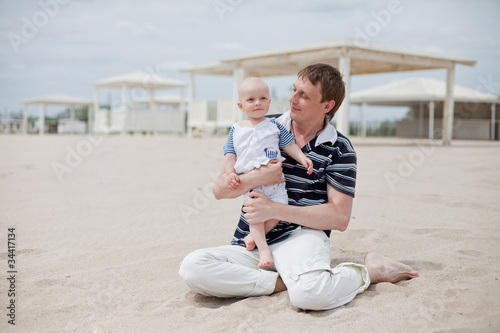 Happy father holding his son at the beach