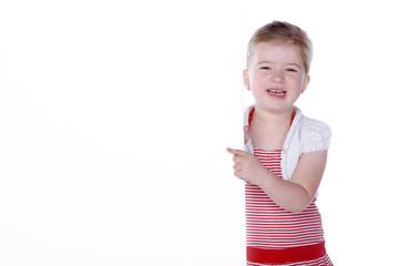 Junges Mädchen blickt lächelnd und zeigt auf Wand