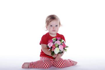 Kleines Mädchen sitzt am Boden mit Blumenstrauß, quer