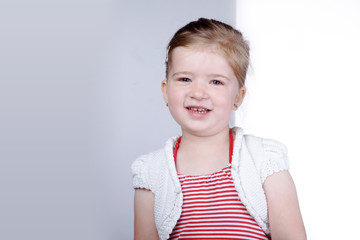 Junges Mädchen steht vor Tafel und lacht