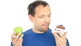 Man thinking what to eat between an apple and a cake, isolated