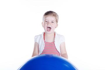 Junges Mädchen spielt mit großem Ball und schreit