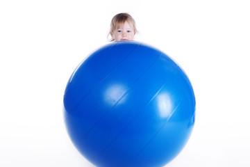 Kleines Kind hinter großem Ball