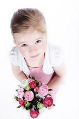 Junges Mädchen blickt mit Blumenstrauß nach oben