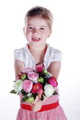 Junges Mädchen überreicht lachend Blumenstrauß