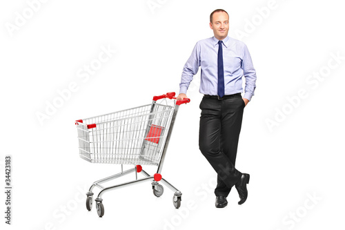 Full length portrait of a man posing next to an empty shopping c