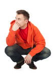 squats young man in orange sweatshirt  full length, series