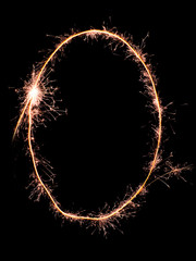 Digit 0 made of sparklers isolated on black.