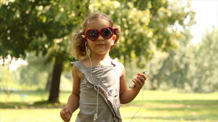 little girl listening music and dancing