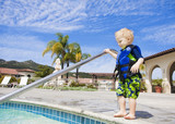 Little Boy Cautiously Stepping into Outdoor Pool
