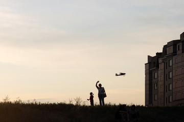 woman, boy and model of aircraft on sunset