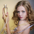 Portrait of beautiful and sexy woman with perfume bottle