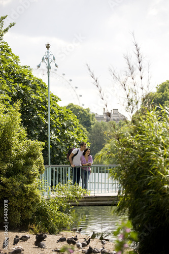 A young couple standing on a bridge in St James Park