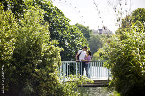 A young couple standing on a bridge, looking at each other