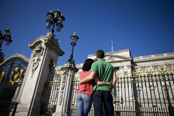 A young couple standing in front of Buckingham Palace, rear view