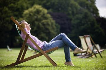 A young woman sitting on a deckchair, enjoying the sunshine