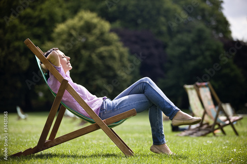 A young woman sitting on a deckchair, enjoying the sunshine