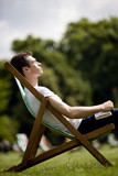 A young man sitting on a deckchair, enjoying the sunshine