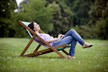 A young woman relaxing on a deckchair in St James Park