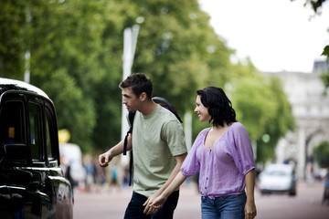 A young couple talking to a taxi driver