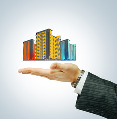 Buildings in businessman's hand
