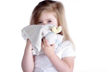 Junges Mädchen blickt traurig hinter Kuschelbär hervor