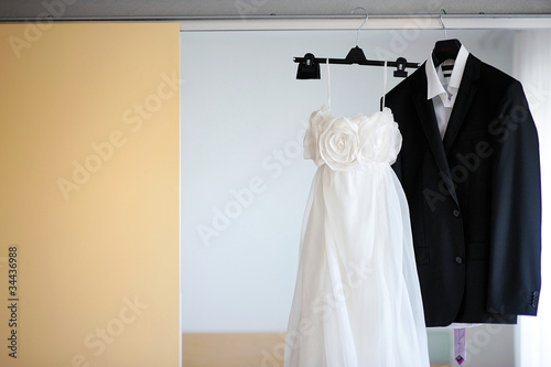 Wedding dress and a tuxedo hanging on a shoulders