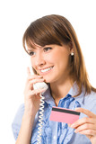 Young businesswoman with plastic card, on cellphone, isolated
