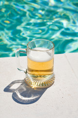 glass of cold beer on pool board in hot summer day