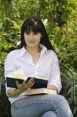 Junge attraktive Frau mit Büchern im Garten
