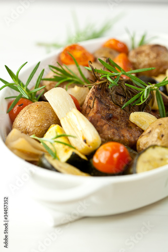 Rustic meat dish with rosemary sprigs