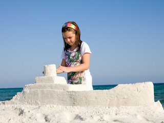Girl playing by ocean sculpturing boat