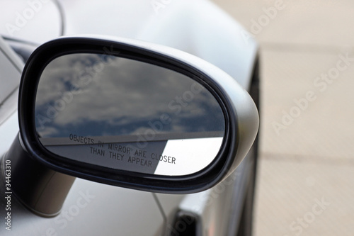 racing car mirror with reflection of clouds